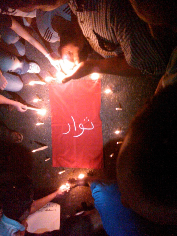 "Family members and supporters laid candles next to a cloth with the word for ""Revolutionaries"" embroidered in the middle"